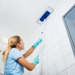 Woman Cleaning The Ceiling Of The Bathroom With Mop