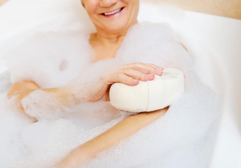 Bathing woman relaxing with sponge.