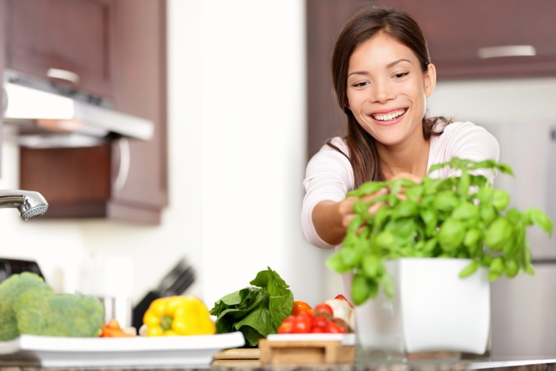 Woman making food in kitchen reaching for basil plant. Healthy eating concept with beautiful happy smiling multi-racial Caucasian / Asian woman at home.