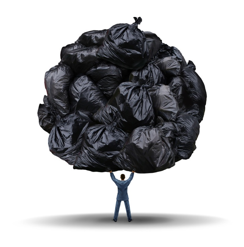 Clutter management business concept as a businessman lifting up a group of garbage bags as a leadership metaphor for cleaning up corporate waste and cutting company fat or getting rid of exess.