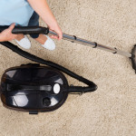 Close-up Of Woman Vacuuming Carpet At Home