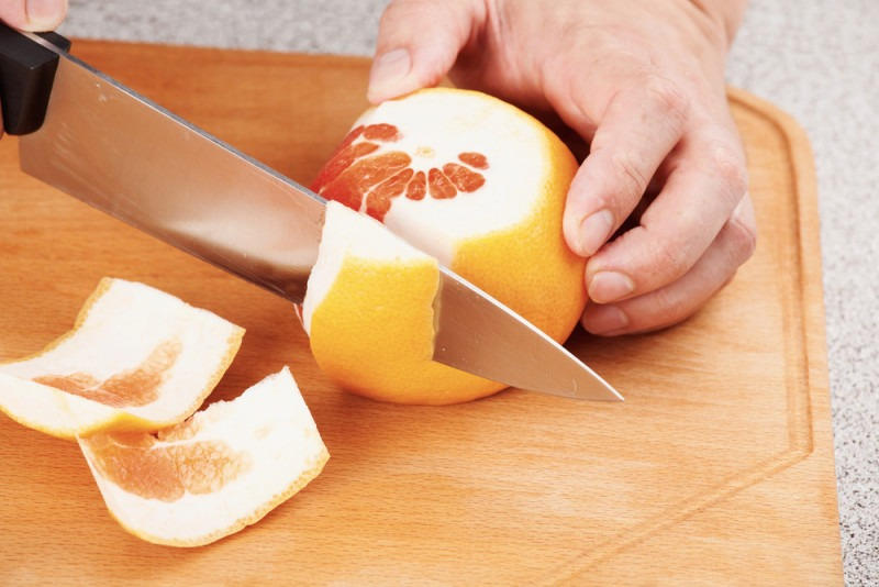 Cutting with grapefruit rind with a knife on a cutting board. Cleaning citrus peel from