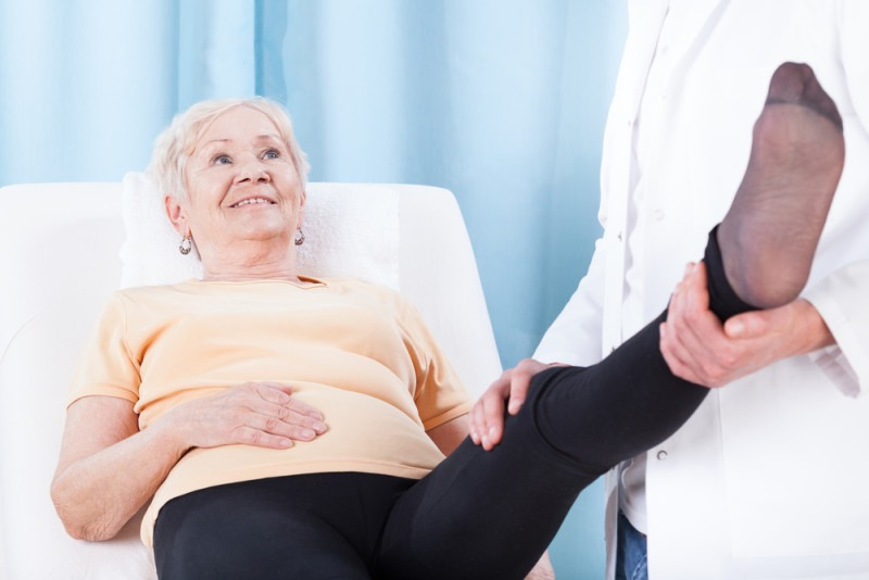 Elderly woman during leg rehabilitation in hospital