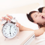 Wake up - Tired couple touch the alarm clock while they are sleeping in bed, asian family