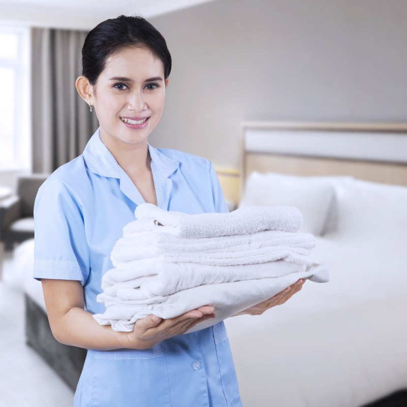 Smiling young cleaning lady holding towels shooting at hotel room