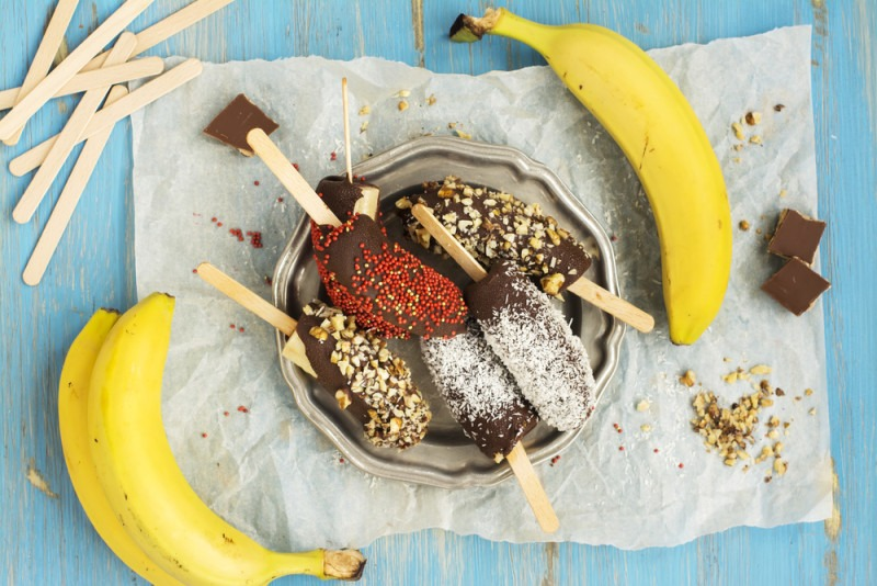 Frozen homemade banana pops covered with chocolate, sprinkles, nuts and coconut chips. Top view