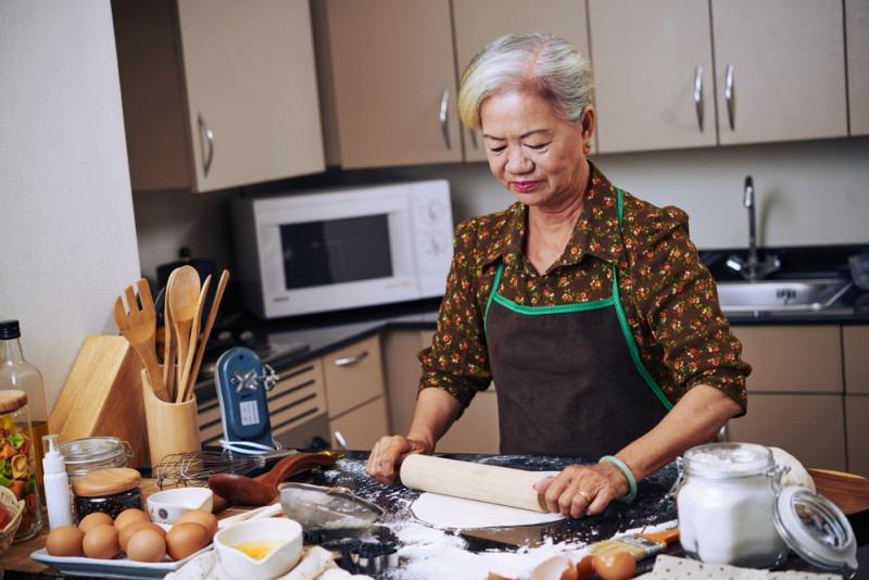 Senior Vietnamese woman cooking in her kitchen