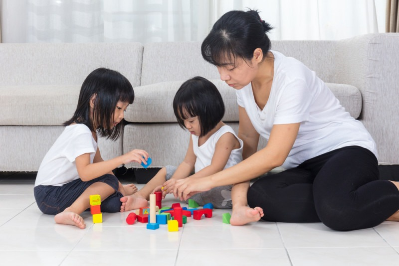 Asian Chinese mother and daughter playing blocks on the floor