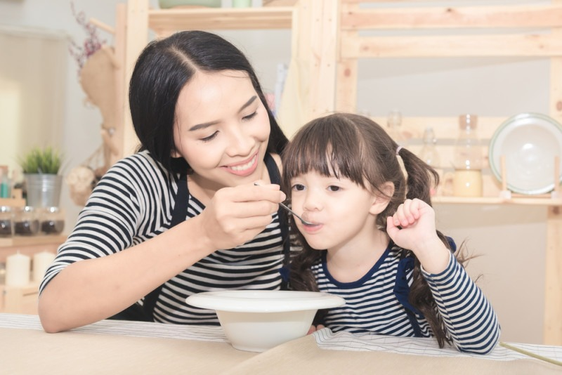 Happy family of asian mom feeding healthy breakfast to her cute