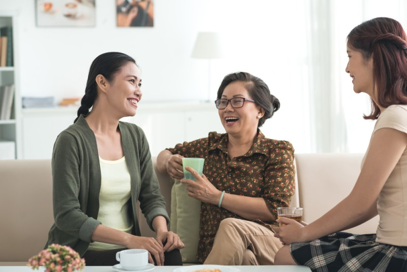 Grandmother, mother and daughter drinking tea and having good time together