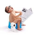 Little boy with glasses, sitting on potty and having fun with newspaper
