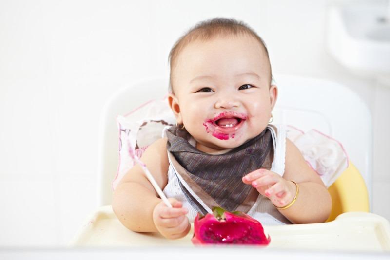 baby girl eating red dragon fruit