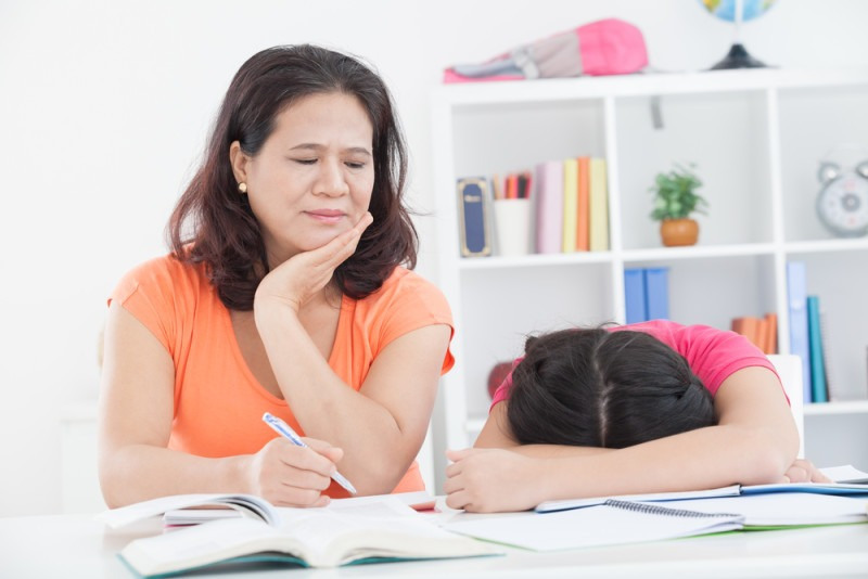 A tired mother and her daughter doing homework inside