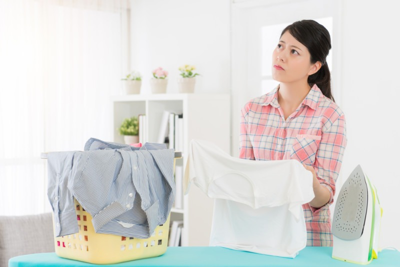 elegant young female student girl standing in front of ironing board and holding clothing feeling bored about helping mother doing housekeeping at home.