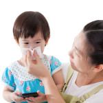 Asian mother carrying and blowing nose her daughter,child holding electronic gadget ,isolated on white background