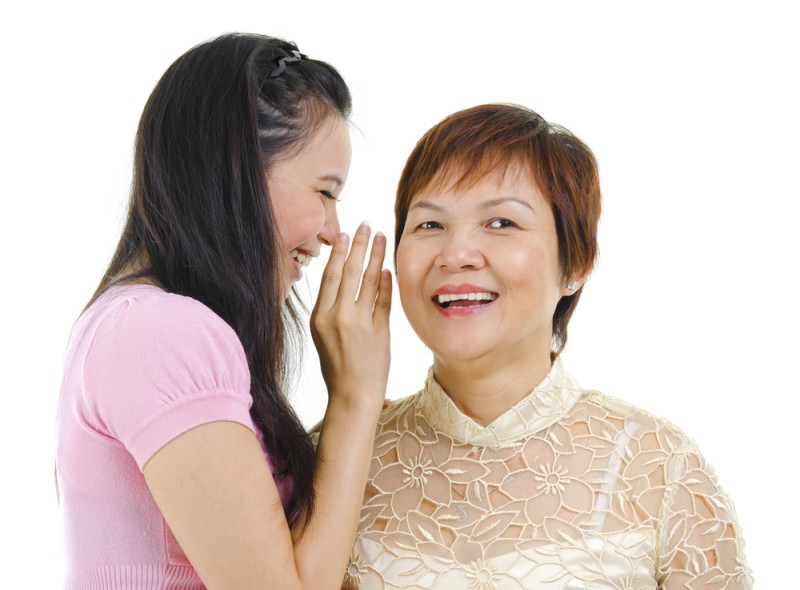Young Asian daughter talking secretly to her mum