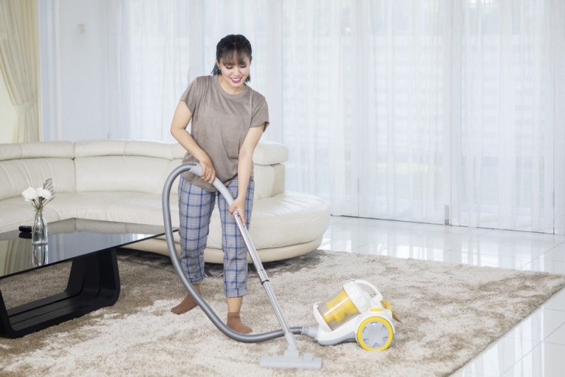 Asian woman cleans carpet with a vacuum cleaner